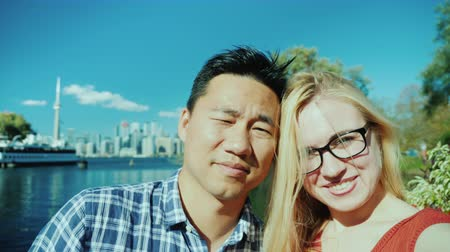 multirracial : Happy couple doing selfie on the background of Toronto. Tourism and traveling in Canada concept