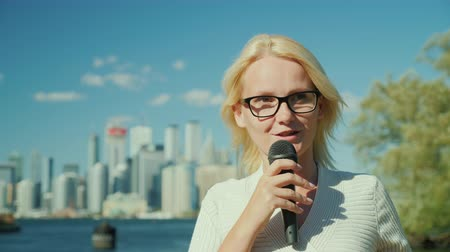 jornalista : A woman journalist and TV presenter speaks into a microphone on a city background. Toronto, Canada