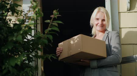 kurier : A woman with a parcel is standing on the threshold of her house. Looks at the camera, smiling. Delivery of parcels to the door