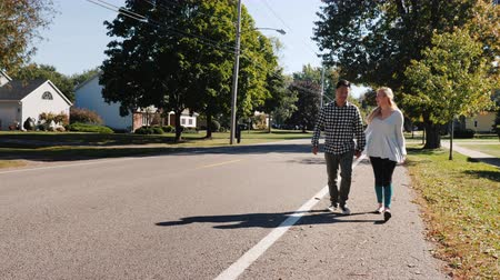 окрестности : Young couple walking down the street holding hands. Typical American city Стоковые видеозаписи