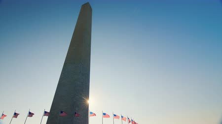 bluestone : The sun appears because of the Washington monument. American flags flap below Stock Footage