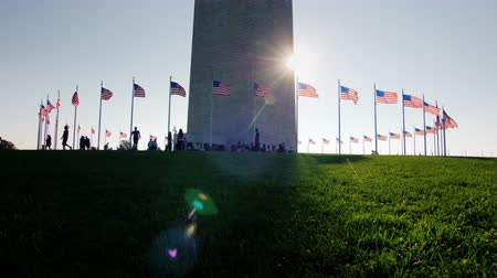 comemoração : People are resting near the Washington Monument in the very center of the American capital. The sun shines because of the obelisk