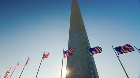 bluestone : Tilt shot: The sun appears because of the Washington monument. American flags flap below Stock Footage