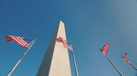 bluestone : Low angle shot Washington monument in DC, USA, American flags flap below