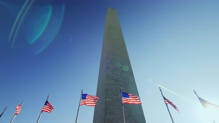 bluestone : The Washington Monument, a sunny flare from the flag that flutters in the wind