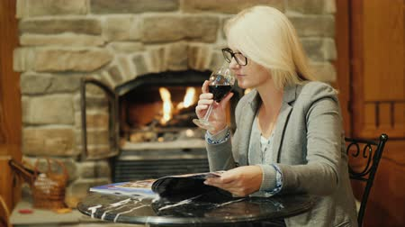 časopis : A woman with a glass of red wine is resting in the restaurant. Looks at the magazine on the table