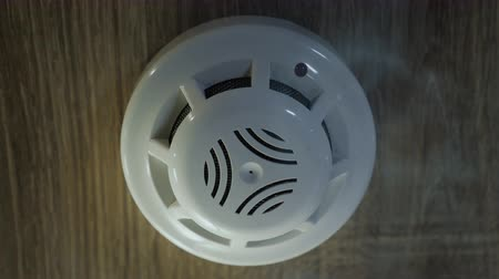 тревожный : Smoke trickles above the ceiling. Smoke detector with flashing red indicator