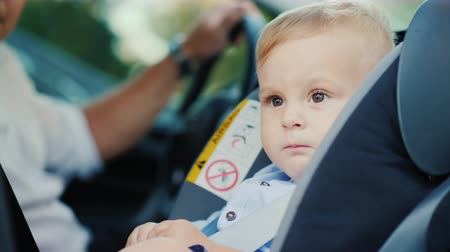 restraint : Portrait of a cute little boy boy, sits in a childrens car seat near the pope. Safety and child care concept