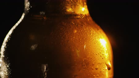 beautifully : A bottle of cold beer on a black background. A ray of light beautifully illuminates it, it slowly rotates