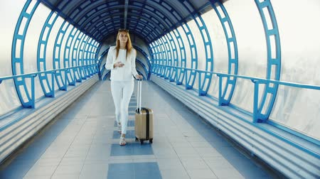 bagagem : Stylish business woman in white suit goes through the tunnel, or the transition from the glass. Lucky bag on wheels, holding a mobile phone Vídeos