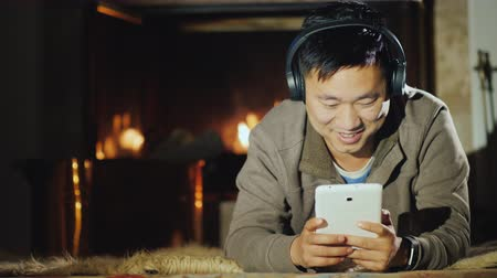 tek başına : Happy Asian man resting at home by the fireplace, enjoys a tablet Stok Video
