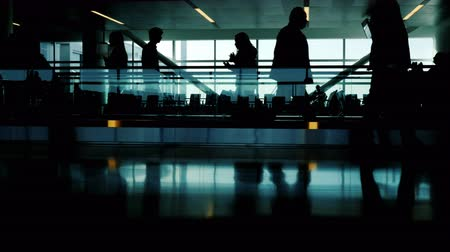 batoh : A crowd of unrecognizable silhouettes of passengers in the airport terminal. Go and go by the moving tape. Life in motion - urban scene Dostupné videozáznamy