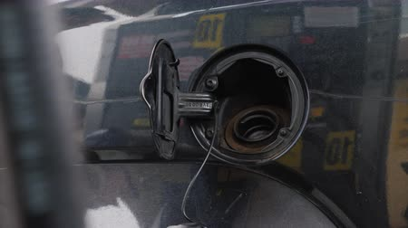 galão : A woman in winter clothes runs her car. Opens the fuel tank cap and inserts the refueling gun
