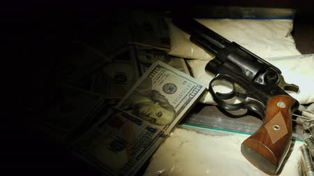 guns : A flashlight beam illuminates a cache of weapons and drugs. Crime and illegal activity concept Stock Footage