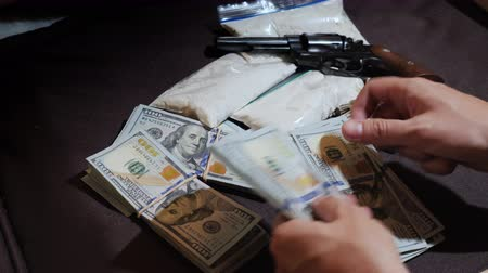 stash : Mens hands count money against the background of weapons and packets of drugs. Dirty money and drug dealing concept