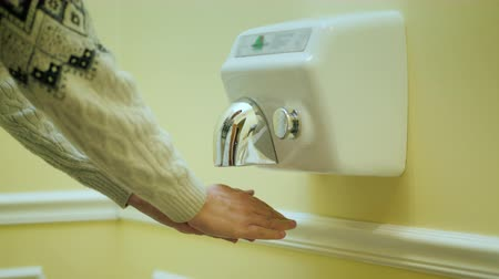 lavatório : The man dries his hands under a stream of hot air. Hand dryer Stock Footage