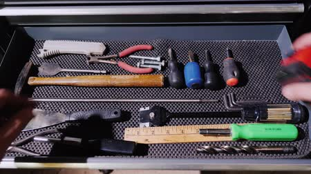 drawer : A male master opens a drawer with tools and takes a tape measure and a hammer Stock Footage