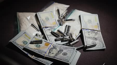 stash : Bullets and a gun fall into a hiding-place, where money and drugs lie. Criminal Business Concept. Slow motion video