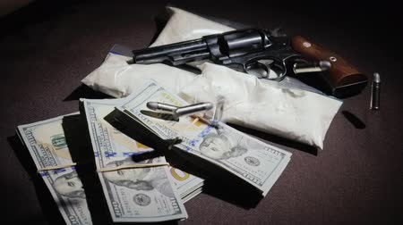 stash : Ammunition to the revolver falls down, where money, weapons and drugs lie. Criminal business, dirty money concept. Slow motion video
