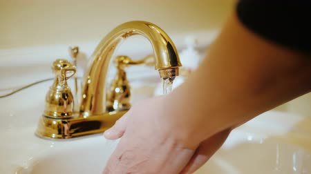 lavatório : A woman washes her hands under the tap. Plumbing and water supply Stock Footage