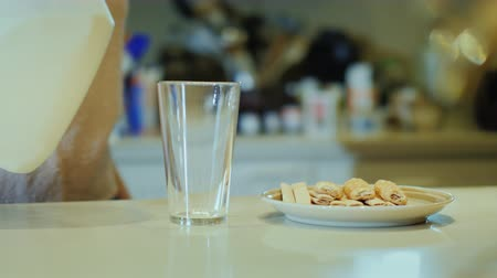 galão : Unrecognizable Woman pours milk into a glass and drinks. A good start to a new day, healthy eating