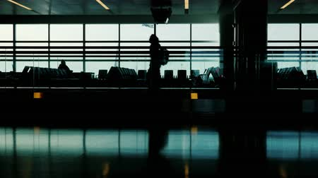 chegada : Silhouette of a passenger hurrying on his flight. Against the background of a large window, behind which is seen a flying aircraft. Do not miss your flight concept
