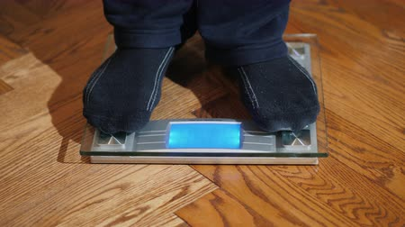 ayak parmakları : A man in homewear is weighed on the scales. Weight Control and Diet Concept Stok Video