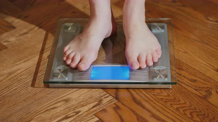 bare foot : A barefoot man measures his weight on a floor scales Stock Footage
