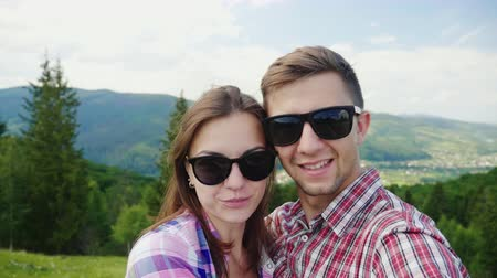 self portrait photography : A happy couple in sunglasses takes pictures of themselves in a picturesque place on the background of the mountains Stock Footage