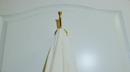 домохозяйка : Low angle video: A white clean towel is hung on the hook. Bath and bath accessories Стоковые видеозаписи