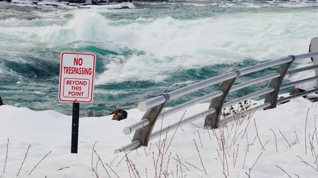 tilalom : A sign with a warning about a dangerous place in the river. The stormy water of the Niagara River in front of the waterfall