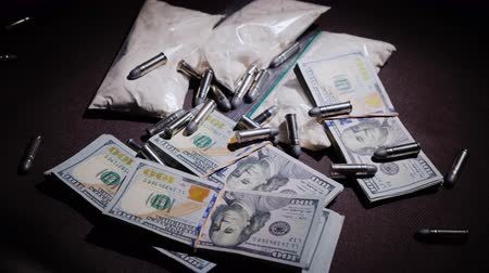 terrorismo : The gun and bullets fall down on the background of money and drugs. Criminal activity concept