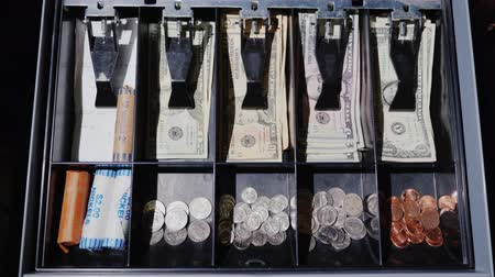 cem : The drawer of the cash desk opens, where cash US dollars and coins lie. View from above