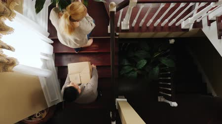 межрасовый : A young multiracial couple is resettled in a new house. They carry their things upstairs, a flowerpot and a box