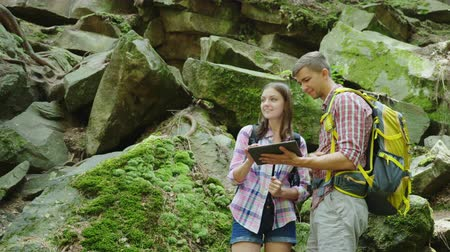 ガールフレンド : Young travelers with backpacks discuss the route. Use a tablet stand near large stones in the woods