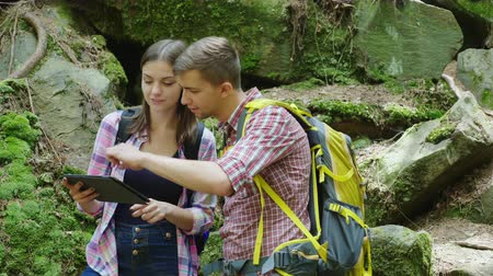 discutir : Young travelers with backpacks discuss the route. Use a tablet stand near large stones in the woods