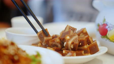 hladový : Take a traditional Chinese dish with chopsticks. Close-up - cubes of meat jelly. Chinese Restaurant and Food Concept