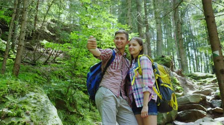 self portrait photography : An attractive couple of tourists are photographed in the forest. Selfie with backpacks on a hike