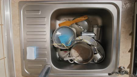 clogged : The sink is filled with dirty dishes. Many dishes need to be washed. Timelapse video