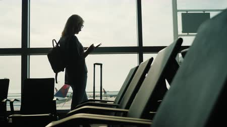 aerodrome : Business woman waiting for a flight. Standing by the window, using a tablet