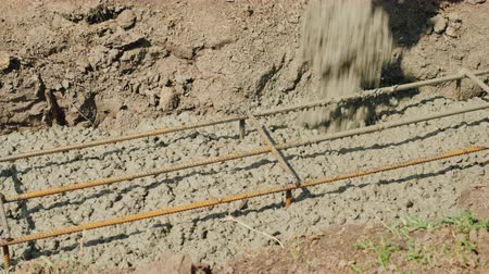 reinforced concrete : The flow of concrete is poured into the foundation of the foundation for the reinforcement. Country building Stock Footage