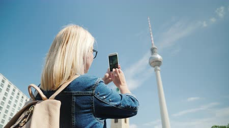 pocztówka : A woman takes photos of the Berlin TV tower. Journey through Berlin and Europe concept