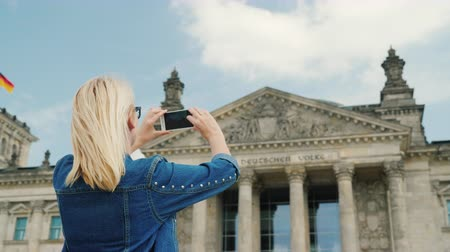 bundestag : A woman tourist takes pictures of the building of the Bundestag in Berlin. Tourism in Germany and Europe concept