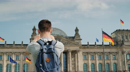 bundestag : The teenager takes pictures of the building of the Bundestag in the center of Berlin. Tourism in Germany concept Stock Footage