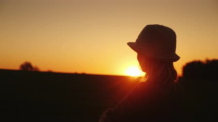 zmiany : A woman in a hat looks forward to the sunset. Hope and bright future concept Wideo
