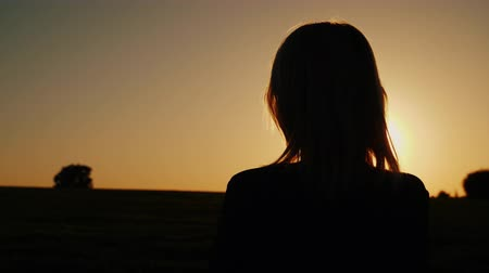végső : A thoughtful woman looks at the setting sun, the back view. Dreams and loneliness concept, look forward