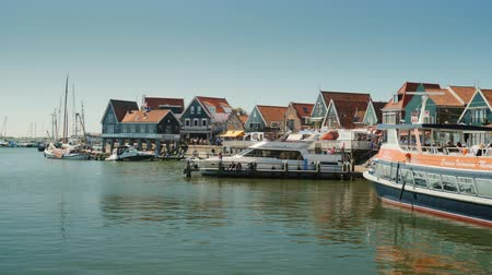 holandês : Volendam, Netherlands, May 2018: Picturesque fishing village in the Netherlands. Ancient houses and boats. On the foreground fly gulls