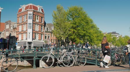 holandês : Amesterdam, Netherlands, May 2018: The active life of Amsterdam is a crossroads with heavy traffic of pedestrians, bicycles and cars. Environmentally friendly transport