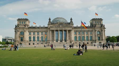 bundestag : Berlin, Germany, May 2018: Tourists are resting near the building of the Bundestag in Berlin on a clear spring day