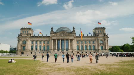 bundestag : Berlin, Germany, May 2018: The building of the Bundestag in Berlin. Near it tourists and locals walk, rest on a green lawn